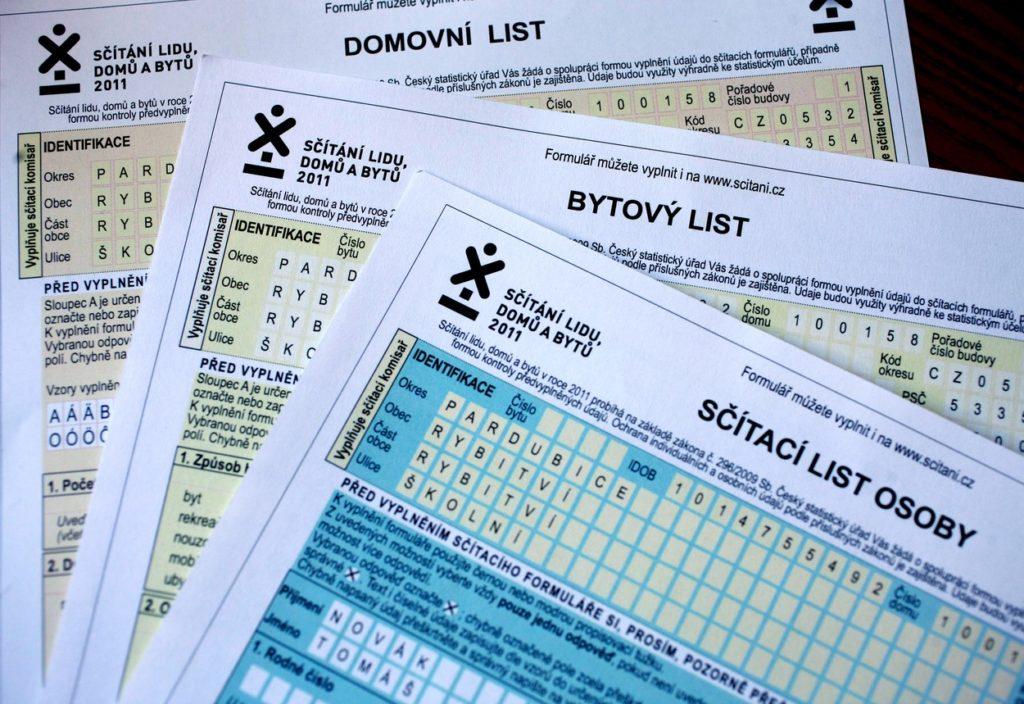 Sčítací komisaři roznášejí listinné formuláře.